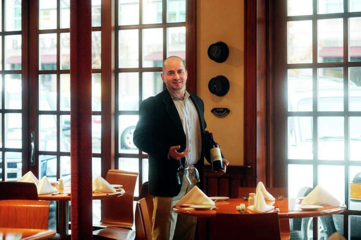 """Mediterraneo manager Edwin Morales stands at one of Regis Philbin's favorite tables at the restaurant on Greenwich Avenue, on Tuesday, Jan. 18, 2011. Philbin announced Tuesday he would be retiring from """"Live With Regis and Kelly,"""" the morning show he's hosted for more than a quarter-century, at the end of the summer."""