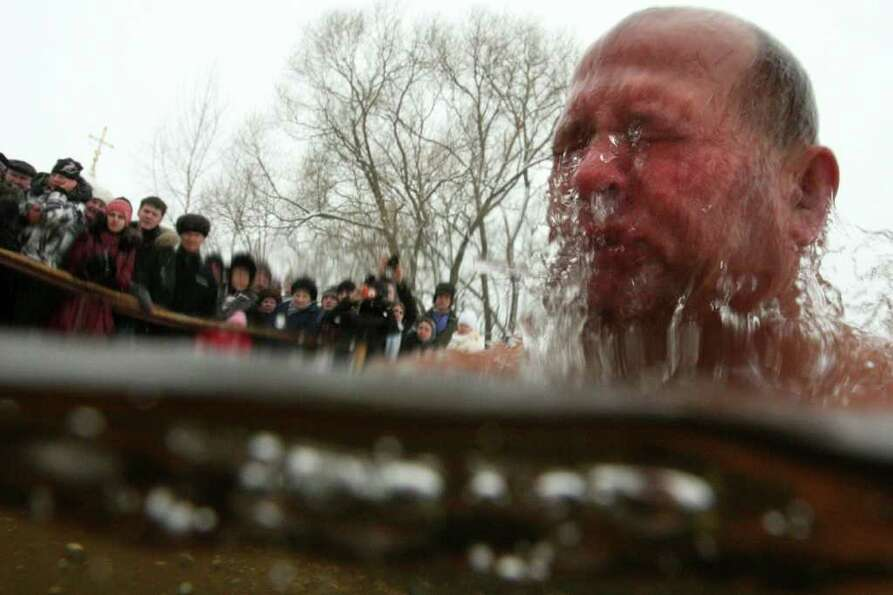 People watch a Russian Orthodox believer plunging into icy waters in celebration of the Epiphany hol