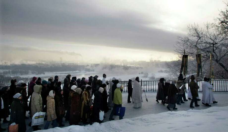 Russian orthodox believers march towards an ice hold during a religious procession to mark the Epiphany at Kolomenskoe park, on the outskirts of Moscow, Russia, Wednesday, Jan. 19, 2011. Thousands of Russian Orthodox Church followers plunged Tuesday and Wednesday into icy rivers and ponds across the country to mark the upcoming Epiphany, cleansing themselves with water deemed holy for the day. Moscow temperatures on Wednesday dropped to -14 Celsius (7 Fahrenheit). (AP Photo/Mikhail Metzel) Photo: Mikhail Metzel / AP