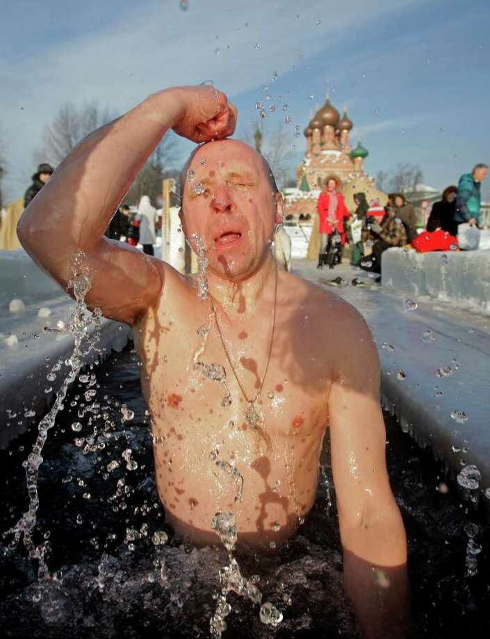 A Russian crosses himself as he emerges from an ice hole made in the shape of a cross in a traditional Epiphany celebration in Moscow, Wednesday, Jan. 19, 2011. Thousands of Russian Orthodox Church followers plunged into icy rivers and ponds across the country to mark the  Epiphany, cleansing themselves with water deemed holy for the day. Water that is blessed by a cleric on Epiphany is considered holy and pure until next year's celebration, and is believed to have special powers of protection and healing. The Russian Orthodox Church follows the old Julian calendar, according to which Epiphany falls on Jan. 19.  Moscow temperatures on Wednesday morning dropped to -13 C ( 9 F). (AP Photo/ Alexander Zemlianichenko Jr) Photo: Alexander Zemlianichenko Jr / AP