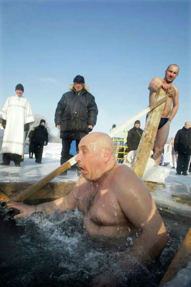 A man emerges from cold water after plunging into the ice hole of the pond in the Kolomenskoe park on the outskirts of Moscow, Russia, Wednesday, Jan. 19, 2011. Thousands of Russian Orthodox Church followers plunged Tuesday and Wednesday into icy rivers and ponds across the country to mark the upcoming Epiphany, cleansing themselves with water deemed holy for the day. Water that is blessed by a cleric on Epiphany is considered holy and pure until next year's celebration, and is believed to have special powers of protection and healing. The Russian Orthodox Church follows the old Julian calendar, according to which Epiphany falls on Jan. 19. Moscow temperatures on Wednesday dropped to -14 C ( 7 F). (AP Photo/Mikhail Metzel) Photo: Mikhail Metzel / AP