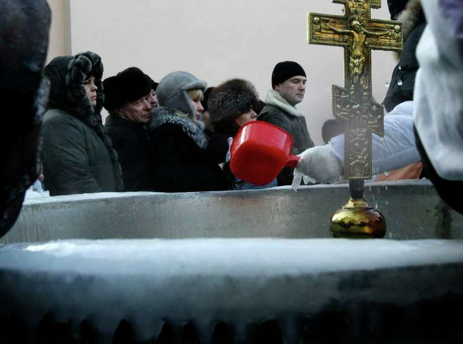 Russian believers queue to receive holy water at Epiphany Cathedral, to mark the upcoming Epiphany in Moscow, Wednesday, Jan. 19, 2011. Water that is blessed by a cleric on Epiphany is considered holy and pure until next year's celebration, and is believed to have special powers of protection and healing. The Russian Orthodox Church follows the old Julian calendar, according to which Epiphany falls on Jan. 19. Moscow temperatures on Wednesday dropped to -14 Celsius (7 Fahrenheit). (AP Photo/Ivan Sekretarev) Photo: Ivan Sekretarev / AP