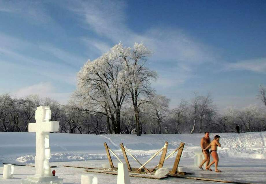 A couple walk away after taking a bath in an ice hole in a pond in Kolomenskoe park, on the outskirts of Moscow, Russia, Wednesday, Jan. 19, 2011. Thousands of Russian Orthodox Church followers plunged Tuesday and Wednesday into icy rivers and ponds across the country to mark the upcoming Epiphany, cleansing themselves with water deemed holy for the day. Moscow temperatures on Wednesday dropped to -14 Celsius (7 Fahrenheit). (AP Photo/Mikhail Metzel) Photo: Mikhail Metzel / AP