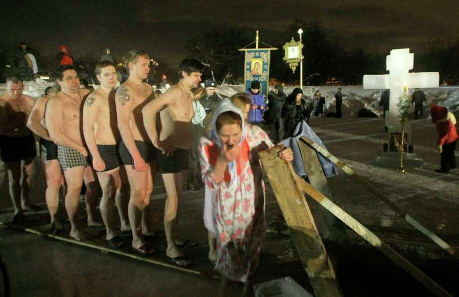People stand in the queue to the bath of the ice cold water in the ice hole of the pound in the Kolomenskoe park on the outskirts of Moscow, Russia, Wednesday, Jan. 19, 2011. Thousands of Russian Orthodox Church followers plunged Tuesday and Wednesday into icy rivers and ponds across the country to mark the upcoming Epiphany, cleansing themselves with water deemed holy for the day. Water that is blessed by a cleric on Epiphany is considered holy and pure until next year's celebration, and is believed to have special powers of protection and healing. The Russian Orthodox Church follows the old Julian calendar, according to which Epiphany falls on Jan. 19. Moscow temperatures on Wednesday night dropped to -14 C ( 7 F). (AP Photo/Mikhail Metzel) Photo: Mikhail Metzel