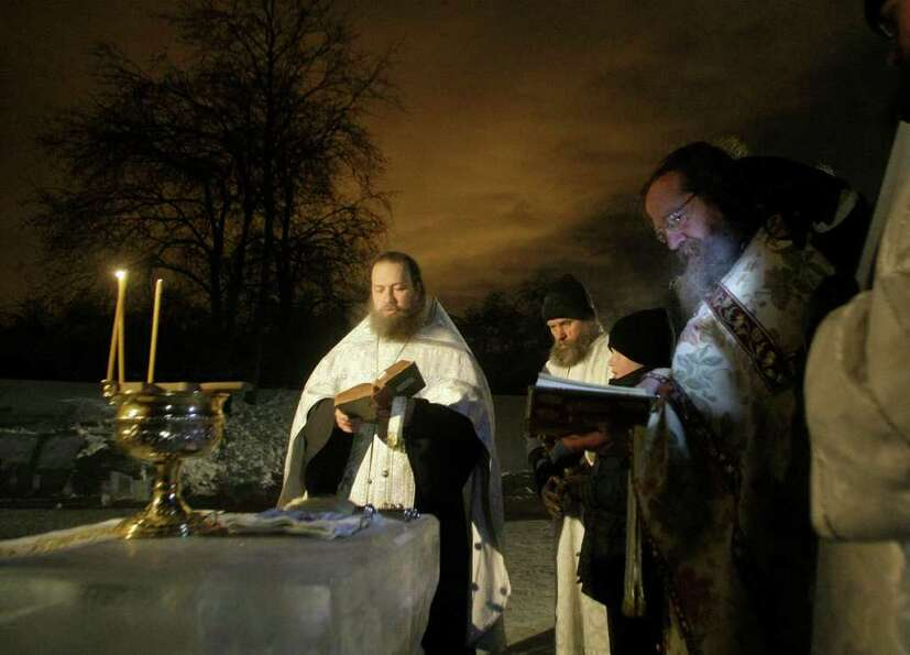 Orthodox priests conduct a service at the ice hole of the pound in the Kolomenskoe park on the outsk