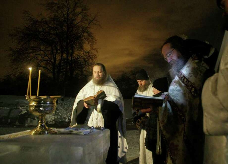 Orthodox priests conduct a service at the ice hole of the pound in the Kolomenskoe park on the outskirts of Moscow, Russia, Wednesday, Jan. 19, 2011. Thousands of Russian Orthodox Church followers plunged Tuesday and Wednesday into icy rivers and ponds across the country to mark the upcoming Epiphany, cleansing themselves with water deemed holy for the day. Water that is blessed by a cleric on Epiphany is considered holy and pure until next year's celebration, and is believed to have special powers of protection and healing. The Russian Orthodox Church follows the old Julian calendar, according to which Epiphany falls on Jan. 19. Moscow temperatures on Wednesday night dropped to -14 C ( 7 F). (AP Photo/Mikhail Metzel) Photo: Mikhail Metzel