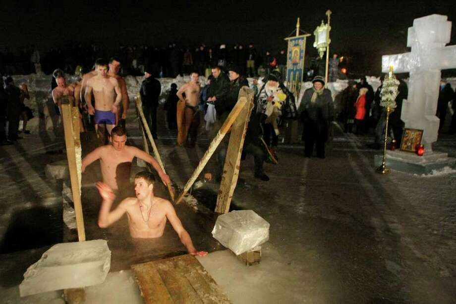 People walk through the bath of the ice cold water in the ice hole of the pound in the Kolomenskoe park on the outskirts of Moscow, Russia, Wednesday, Jan. 19, 2011. Thousands of Russian Orthodox Church followers plunged Tuesday and Wednesday into icy rivers and ponds across the country to mark the upcoming Epiphany, cleansing themselves with water deemed holy for the day. Water that is blessed by a cleric on Epiphany is considered holy and pure until next year's celebration, and is believed to have special powers of protection and healing. The Russian Orthodox Church follows the old Julian calendar, according to which Epiphany falls on Jan. 19. Moscow temperatures on Wednesday night dropped to -14 C ( 7 F). (AP Photo/Mikhail Metzel) Photo: Mikhail Metzel