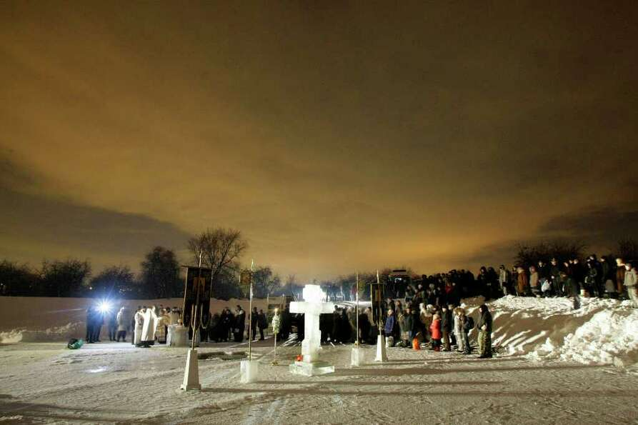 Russian believers gather as orthodox priests conduct a service at the ice hole of the pound in the K