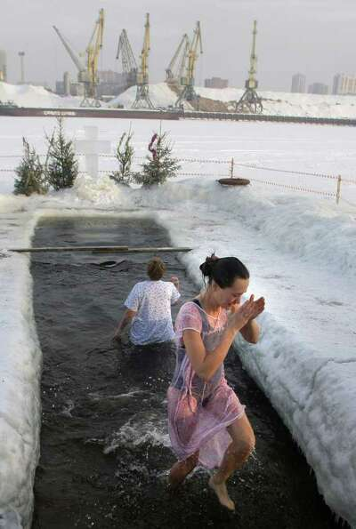 A girl emerges from cold water after plunging into an icy pond to mark the upcoming Epiphany in nort