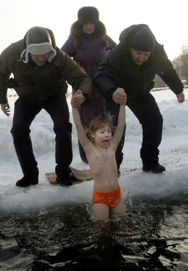 Russian believers lower a young girl into ice cold water to mark the upcoming Epiphany in northwestern Moscow, Tuesday, Jan. 18, 2011. Thousands of Russian Orthodox Church followers plunged Tuesday into icy rivers and ponds across the country to mark the upcoming Epiphany, cleansing themselves with water deemed holy for the day. Water that is blessed by a cleric on Epiphany is considered holy and pure until next year's celebration, and is believed to have special powers of protection and healing. The Russian Orthodox Church follows the old Julian calendar, according to which Epiphany falls on Jan. 19.  Moscow temperatures on Tuesday morning dropped to -13 C ( 9 F). (AP Photo/Mikhail Metzel) Photo: MIKHAIL METZEL / AP