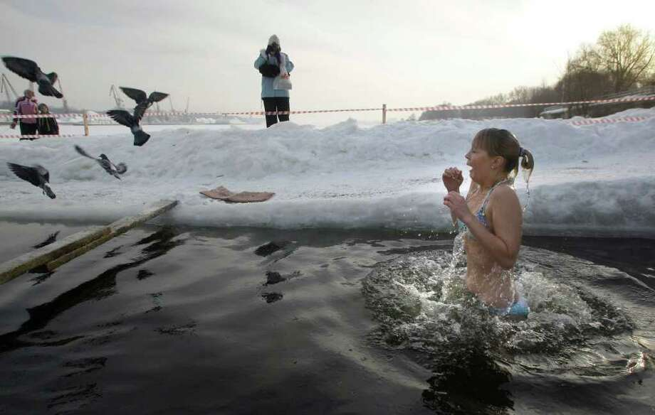 A girl emerges from cold water after plunging into an icy pond to mark the upcoming Epiphany in northwestern Moscow, Tuesday, Jan. 18, 2011. Thousands of Russian Orthodox Church followers plunged Tuesday into icy rivers and ponds across the country to mark the upcoming Epiphany, cleansing themselves with water deemed holy for the day. Water that is blessed by a cleric on Epiphany is considered holy and pure until next year's celebration, and is believed to have special powers of protection and healing. The Russian Orthodox Church follows the old Julian calendar, according to which Epiphany falls on Jan. 19.  Moscow temperatures on Tuesday morning dropped to -13 C ( 9 F). (AP Photo/Mikhail Metzel) Photo: MIKHAIL METZEL / AP