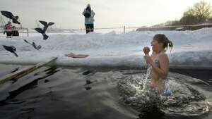 A girl emerges from cold water after plunging into an icy pond to mark the upcoming Epiphany in northwestern Moscow, Tuesday, Jan. 18, 2011. Thousands of Russian Orthodox Church followers plunged Tuesday into icy rivers and ponds across the country to mark the upcoming Epiphany, cleansing themselves with water deemed holy for the day. Water that is blessed by a cleric on Epiphany is considered holy and pure until next year's celebration, and is believed to have special powers of protection and healing. The Russian Orthodox Church follows the old Julian calendar, according to which Epiphany falls on Jan. 19.  Moscow temperatures on Tuesday morning dropped to -13 C ( 9 F). (AP Photo/Mikhail Metzel)