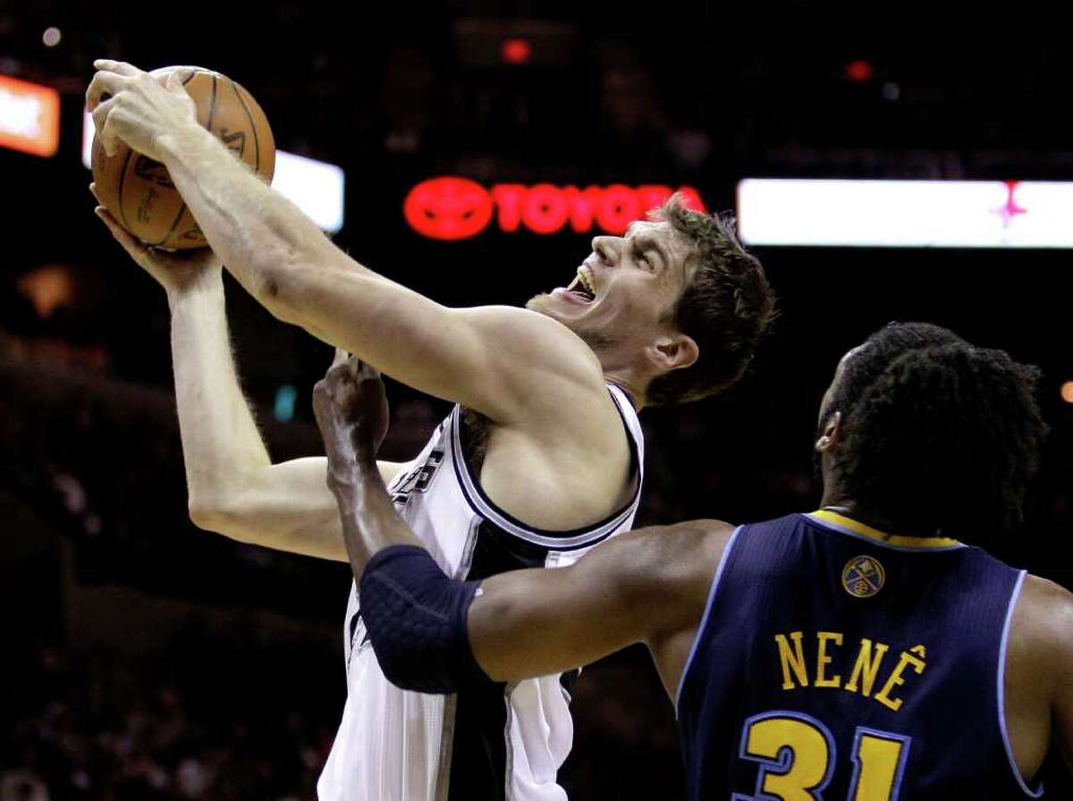 San Antonio Spurs' Tiago Splitter, left, of Brazil, is fouled by Denver Nuggets' Nene (31), of Brazil, during the first quarter of an NBA basketball game, Sunday, Jan. 16, 2011 in San Antonio.