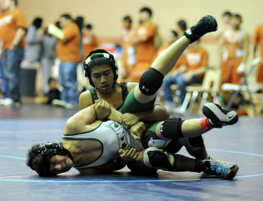 Reagan's Sean Ambrocio tries to turn his opponent during the Reagan Rattler wrestling tournament Saturday. Sean wrestles at in the 112-pound class while younger brother Kevin wrestles in the 119-pound class. Photo: Photo By John Albright