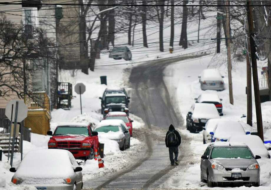 A pedestrian walks up Christie Street in Troy, NY during Tuesday's storm on January 18, 2011. ( Philip Kamrass / Times Union ) Photo: Philip Kamrass
