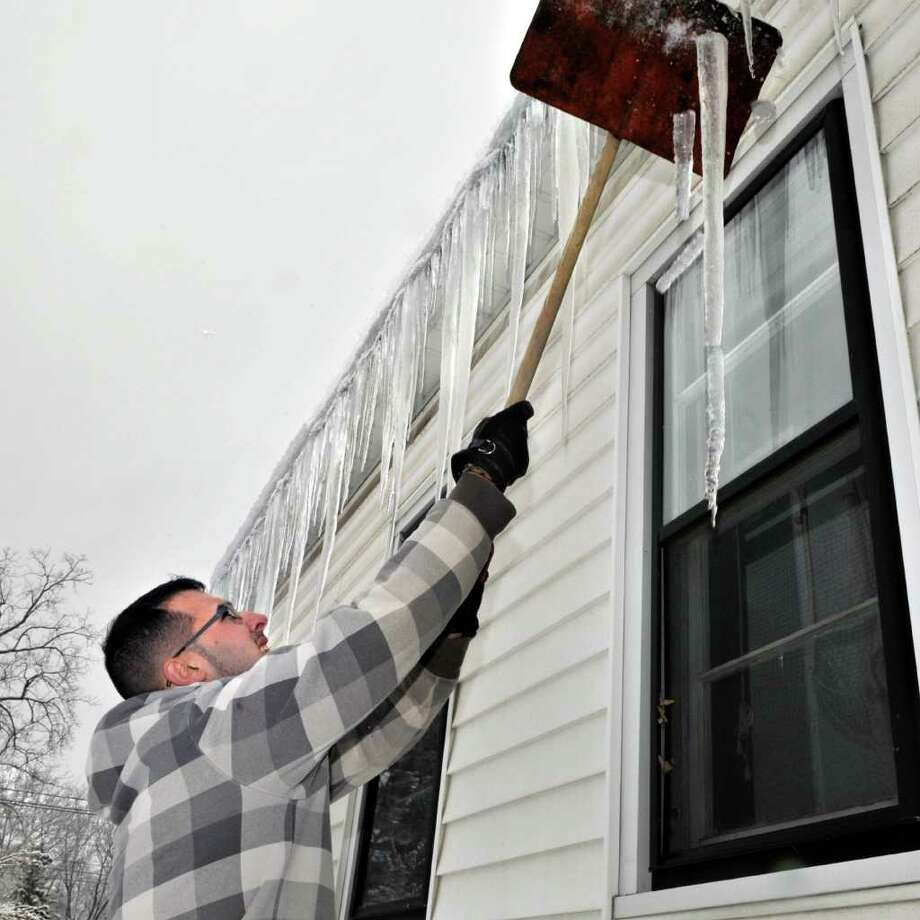 Brian Mascaro knocks ice from his Albany home Wednesday morning January 19, 2011.   (John Carl D'Annibale / Times Union) Photo: John Carl D'Annibale / 00011805A