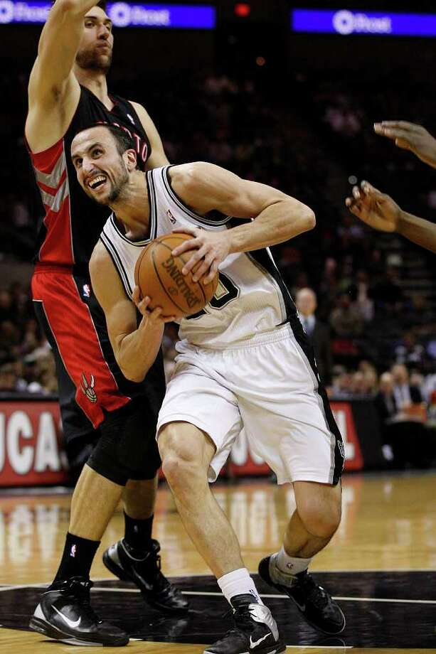 SPURS -- San Antonio Spurs Manu Ginobili tries to get by the defense of Toronto Raptors Andrea Bargnani  during the first half at the AT&T Center, Wednesday, Jan. 19, 2011. JERRY LARA/glara@express-news.net Photo: JERRY LARA, San Antonio Express-News / glara@express-news.net
