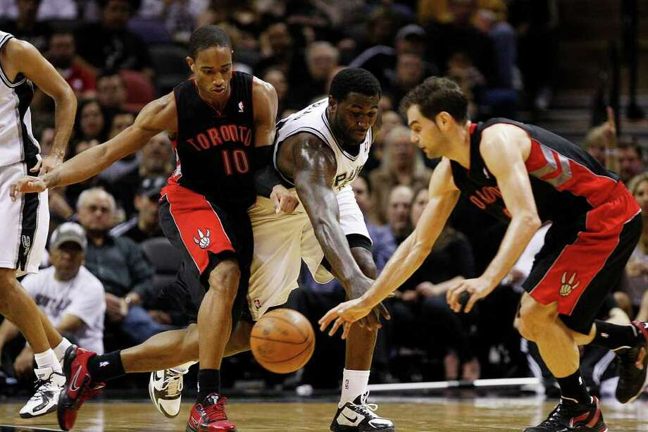 SPURS -- San Antonio Spurs DeJuan Blair tries to steal the ball from Toronto Raptors DeMar DeRozan as Jose Calderon, right, reaches for it during the second half at the AT&T Center, Wednesday, Jan. 19, 2011. The Spur won 104-95 and improve to 36-6. JERRY LARA/glara@express-news.net Photo: JERRY LARA, San Antonio Express-News / glara@express-news.net