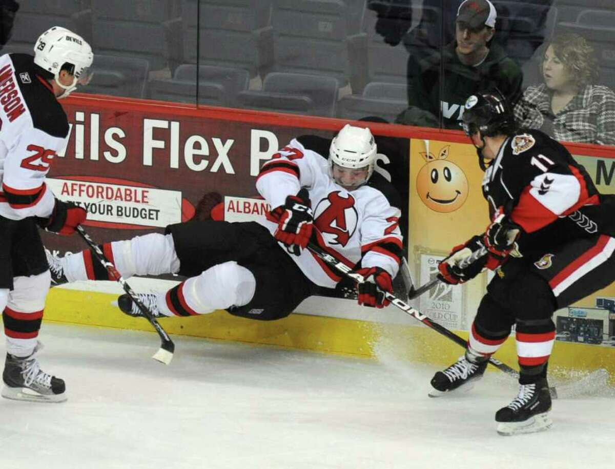 Oliver Magnan of the Albany Devils falls to the ground trying to get the puck from Erik Condra of the Binghamton Senators. (Lori Van Buren / Times Union)