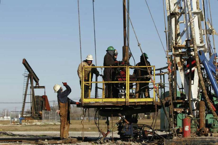 Workers on a workover rig re-completing a well in the West Hastings oil field near an obsolete pump jack, back left, that will be dismantled by Denbury Resources Inc. Photo: Melissa Phillip, Houston Chronicle / Houston Chronicle