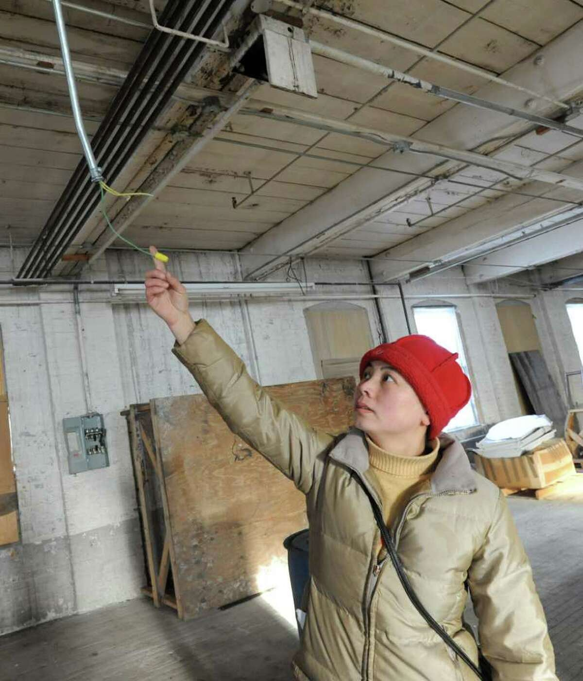 Sarah Cui shows a wire that was deliberately cut at a warehouse where vandalism occurred to property owned by Buddhist community in Amsterdam, NY on January 20, 2011. (Lori Van Buren / Times Union)