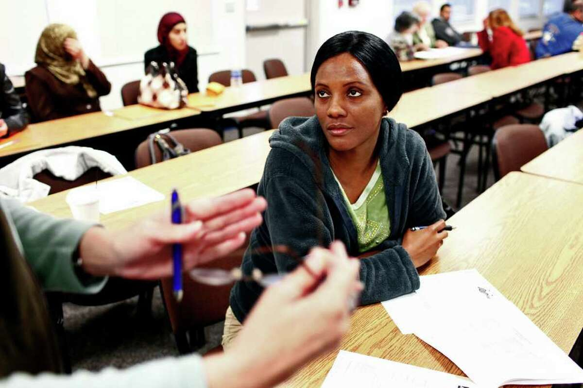 Harlene Egli, who came to the United States from the Democratic Republic of Congo 13 years ago, listens to teacher Alison Williams as Egli signs up for the PACE program at the Northside Learning Center.