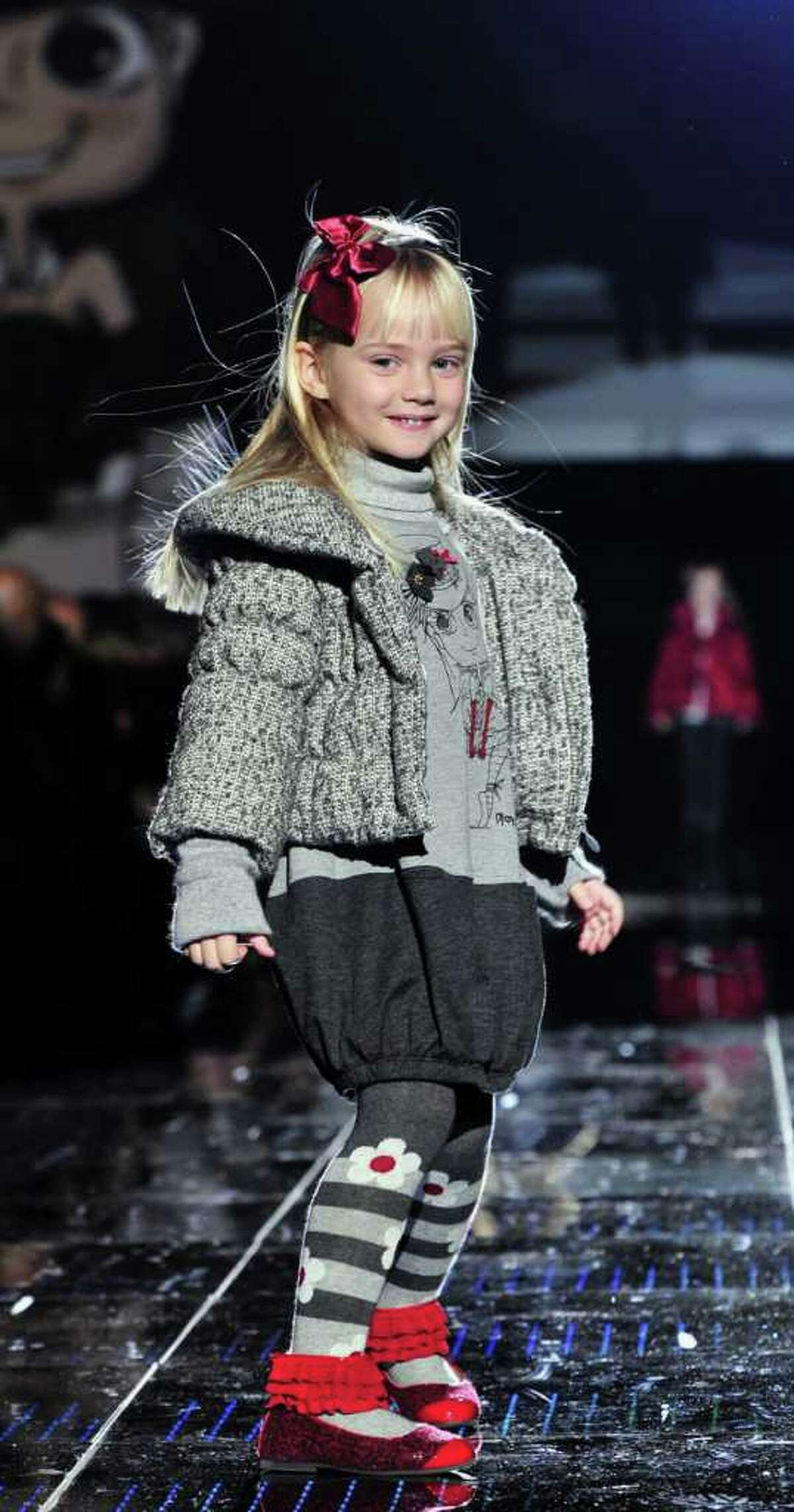 In this photo made available on Friday, Jan. 21, 2011, a model presents a creation of the collection of Italian design label Monalisa at the annual 'Pitti Bimbo' fashion show for children, in Florence, Italy, Thursday, Jan. 20, 2011.