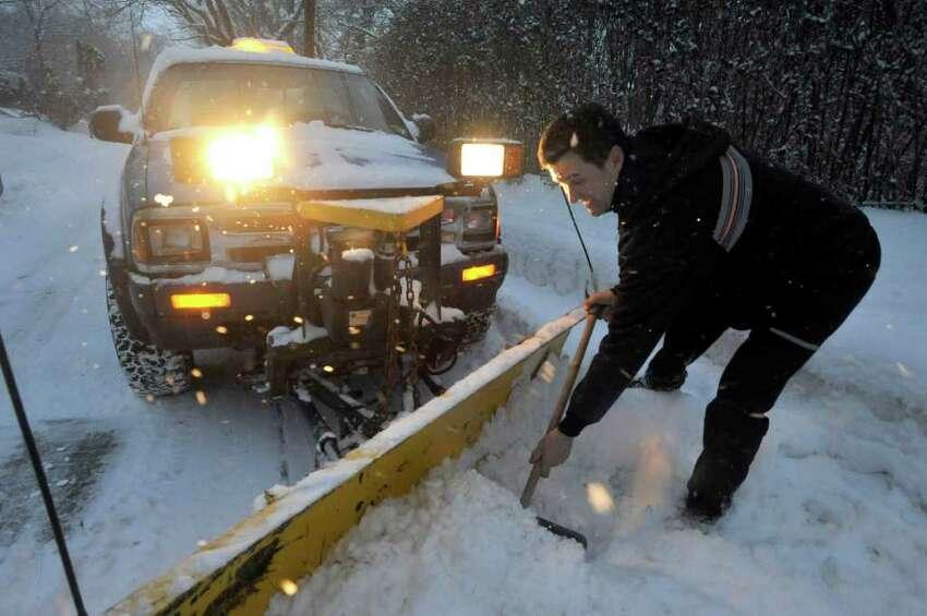 Joe Schleis clears his plow before dawn in Danbury, Friday, Jan. 21, 2010.