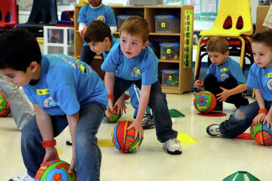 Kids at Children's Lighthouse at Alamo Ranch take part in a program called TOT or Teams of Tomorrow Wednesday January 19, 2011. The program is a training program that uses basketball handling to enhance focus, reinforce educational concepts, develop athletic skills and build self esteem. The boy in the center of the picture is Tate Chisholm,4. JOHN DAVENPORT/jdavenport@express-news.net Photo: JOHN DAVENPORT, Jdavenport@express-news.net / San Antonio Express-News