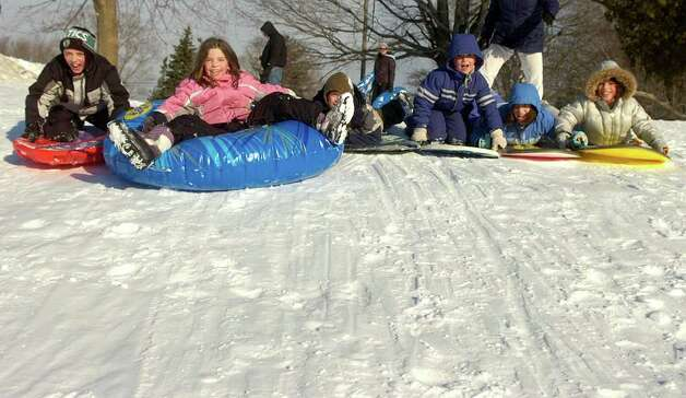 From left, Matthew Bruening, 11; Laura Bruening, 9; Sal DiNardo, 10; Daniel Loboncz, 8; Sophie Loboncz, 8, and Rachel Loboncz, 8, make a chain and sled togetheron the hill behind the John B. Nichols Community Center in Trumbull on Friday, January 21, 2011. Photo: Lindsay Niegelberg / Connecticut Post