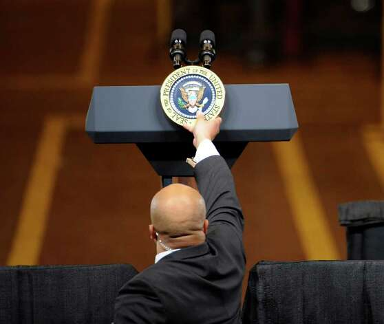 A Secret Service Agent places the Presidential Seal on the podium where President Barak Obama addressed a gathering of workers and dignitaries at the GE plant in Schenectady January 21, 2011.   (Skip Dickstein / Times Union) Photo: SKIP DICKSTEIN / 00011832A