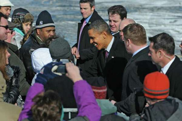 U.S. President Barack Obama shakes hands with spectators after Air Force One landed at the Albany International Airport in Colonie, NY on January 21, 2011. The President is scheduled for a brief tour of the General Electric Plant in Schenectady. (Lori Van Buren / Times Union)