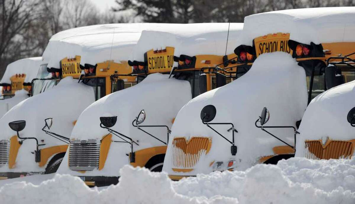 School busses are covered in snow at Amaral Motors in Newtown Wednesday, January 12, 2011.
