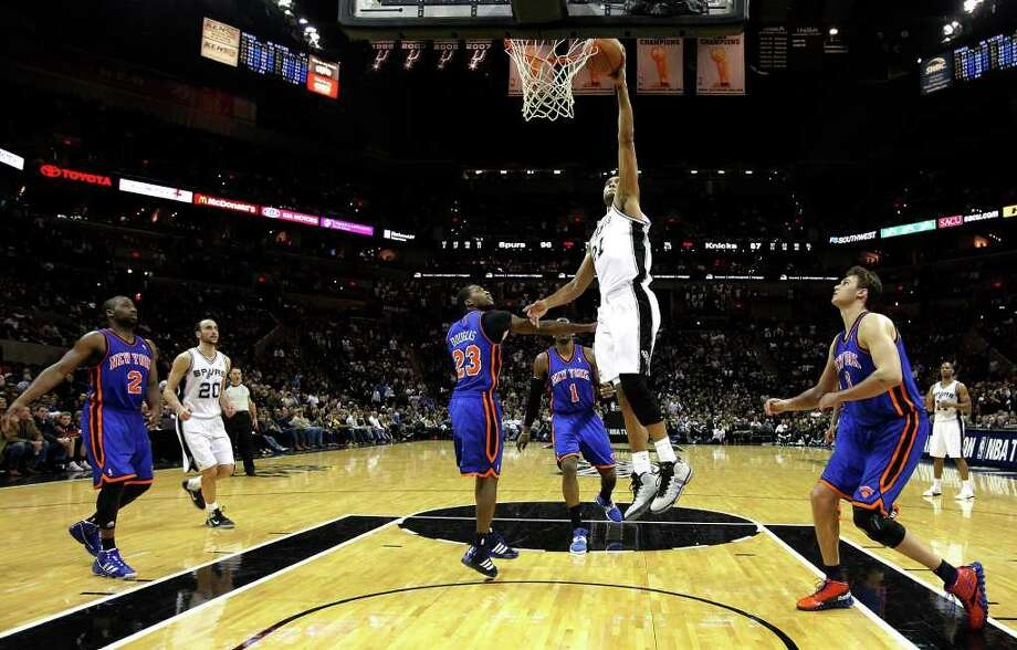 Spurs' Tim Duncan goes in for a dunk against New York Knicks' Toney Douglas (23) in the second half at the AT&T Center on Friday, Jan. 21, 2011. Spurs defeated the Knicks, 101-92. Kin Man Hui/kmhui@express-news.net Photo: KIN MAN HUI, SAN ANTONIO EXPRESS-NEWS / kmhui@express-news.net