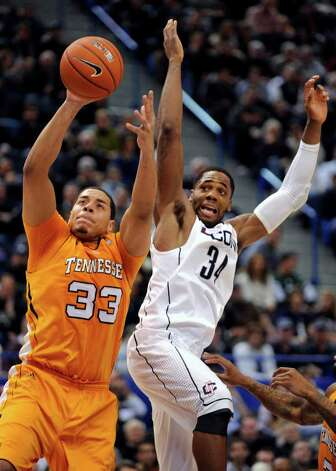 Connecticut's Alex Oriakhi, right, fights for a rebound with Tennessee's Brian Williams during the second half of No. 8 Connecticut's 72-61 victory in their NCAA college basketball game, Saturday, Jan. 22, 2011, in Hartford, Conn. Oriakhi scored 12 points and had 10 rebounds in the game. (AP Photo/Fred Beckham) Photo: AP