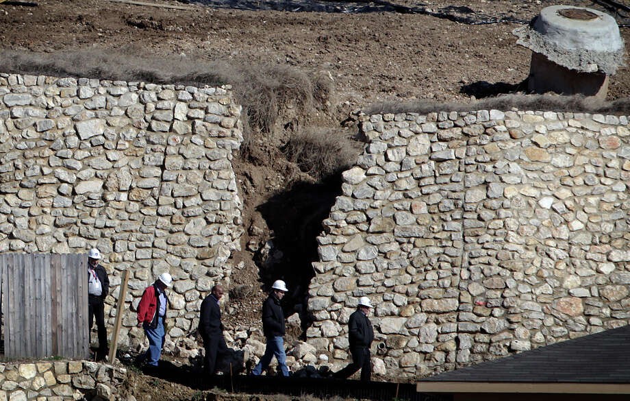 Men in hard hats walk past the fractured retaining wall in the RiverMist subdivision on the city's Northwest side on Friday, Jan. 29, 2010. Photo: Kin Man Hui/kmhui@express-news.net