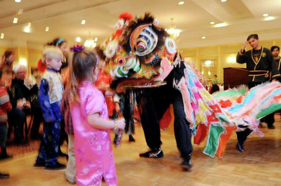 Children feed the lion for luck in the traditional Lion Dance at the Chinese Language School of Connecticut's celebration of the Year of the Rabbit, at the Stamford Plaza Hotel & Conference Center, in Stamford, on Sunday, Jan. 23, 2011. The performers in the Lion Dance were from Kwan's Kung Fu, a traditional school in Peeksville, N.Y. Photo: Helen Neafsey / Greenwich Time