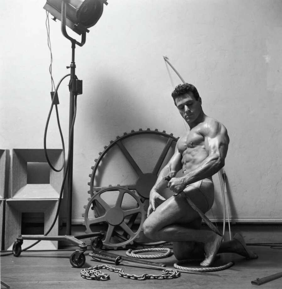 Studio portrait of American bodybuilder and physical fitness expert Jack La Lanne, wearing a swimsuit, holding a sword with other props in the background, 1953. Photo: Graphic House, Getty Images / 2002 Getty Images