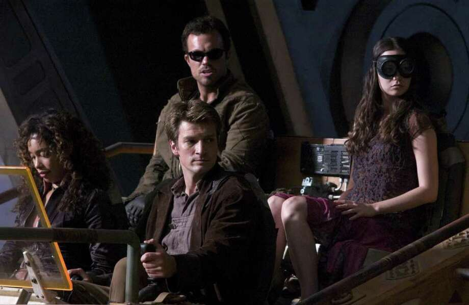 Writer/Director Joss Whedon makes his feature film directorial debut with the futuristic action-adventure Serenity.  Clockwise (from the top), the crew and passengers of Serenity prepare for a dangerous trip off ship: ADAM BALDWIN as Jayne, SUMMER GLAU as River, NATHAN FILLION as Captain Malcolm Reynolds and GINA TORRES as Zoe. (Courtesy photo) Photo: Sidney Baldwin / Copyright,
