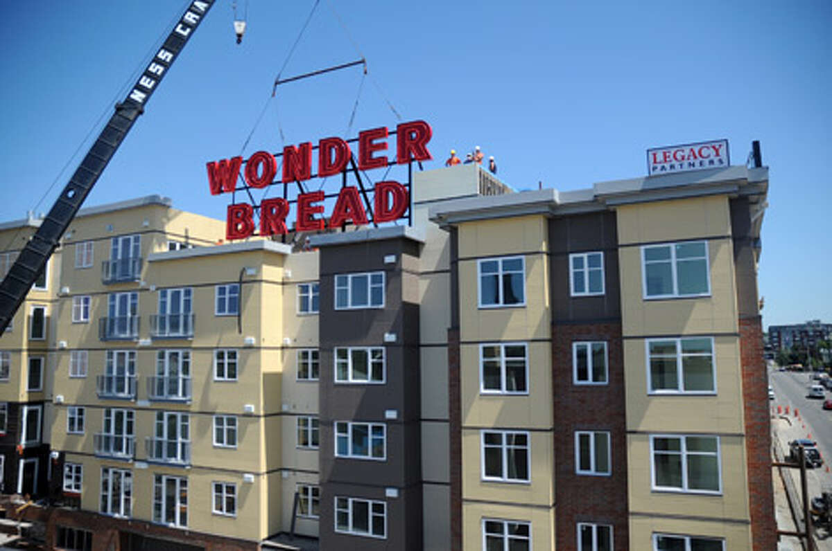 Construction workers align Seattle's famous Wonder Bread sign on top of the Pratt Park apartment building on July 16, 2010. | See a a gallery showing where all 50 cities rank on a list of home prices versus rents.