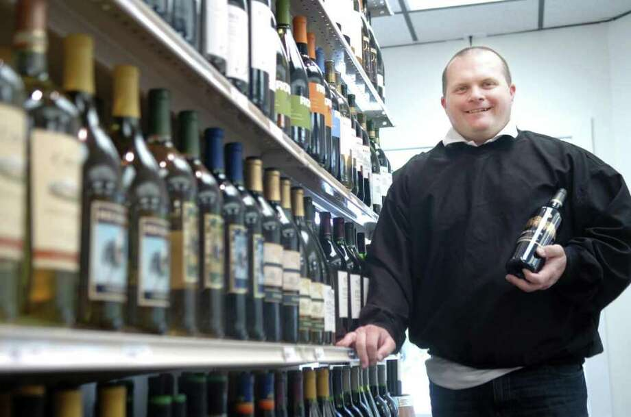 In this May 2009 file photo, Christopher Larson is shown in his new store, Dumpling Pond Wines & Liquor in Riverside. Larson, the former owner of the now-defunct liquor store, is facing criminal charges after police said he ripped off a 90-year-old woman by charging her credit card for liquor purchases she did not make. Photo: File Photo / Greenwich Time File Photo