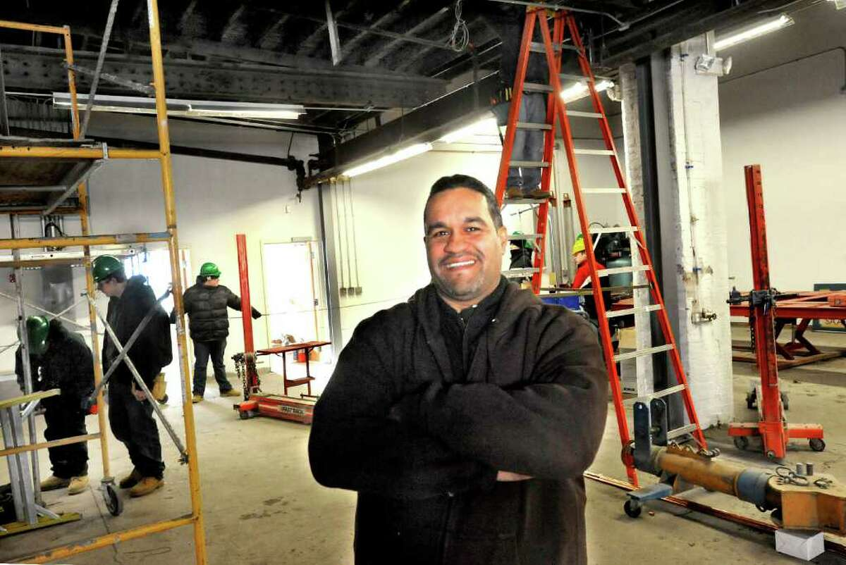 Carlos Espinal stands in his new business, Extreme Auto Body and Collision, in Danbury, Monday, Jan. 24, 2011. Henry Abbott Technical School electrical students work in the background.