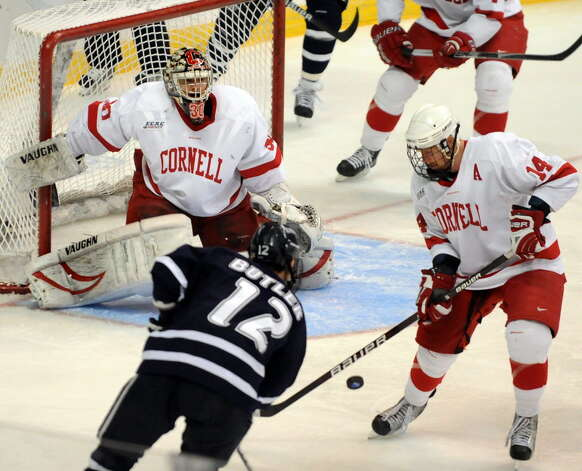 Cornell's goalie Ben Scrivens watches the bouncing puck as teammate Riley Nash, right, and University of New Hampshire's Bobby Butler, left, work the net during their NCAA East Regional hockey game on Friday, March 26, 2010, at Times Union Center in Albany, N.Y. (Cindy Schultz / Times Union archive)