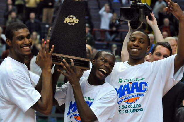 Siena College basketball players Edwin Ubiles, Ronald Moore and Alex Franklin hold the trophy after winning their third straight MAAC Tournament, a 72-65 overtime victory over Fairfield at the Times Union Center in Albany, NY on Monday night March 8, 2010. (Philip Kamrass / Times Union archive)