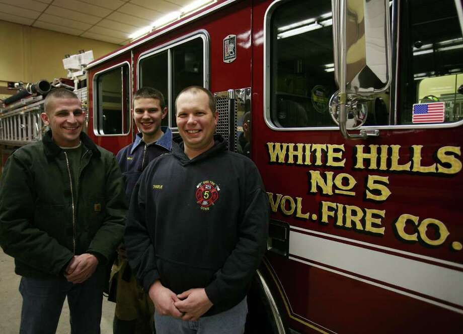 From left; Shelton firefighters Steve Hoffmann, Dan McCue, and Charlie Ovesny at White Hills No. 5 Volunteer Fire Company. Assisted by Hoffmann and McCue, Ovesney rescued a woman from a house fire at 39 Hiawatha Lane in Shelton on Sunday afternoon. Photo: Brian A. Pounds / Connecticut Post