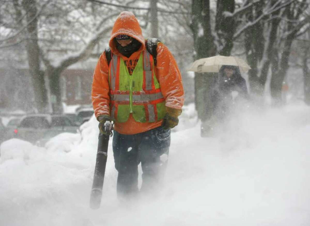 Milford public works employee J.R. Flores uses a handheld blower to keep the sidewalks clear in front of the Parsons Government Complex in downtown Milford on Tuesday, January 25, 2011.