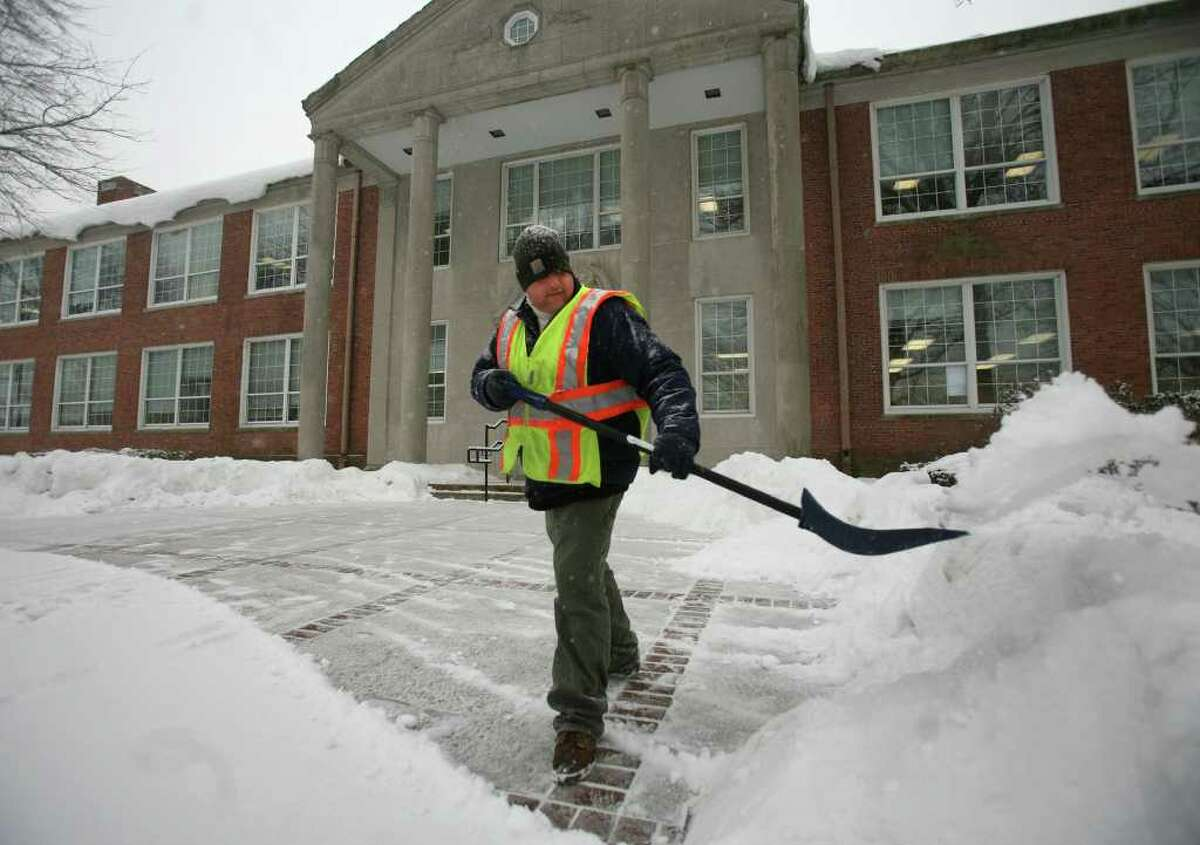 Milford public works employee Brian Wasilnak shovels snow in front of the Parsons Government Complex in downtown Milford on Tuesday, January 25, 2011.