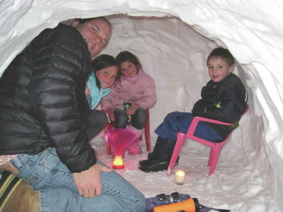 Shedd Glassmeyer and his three children, Annie, Abby and Will, enjoy dinner inside the snow fort they created at their Woods End Road home Photo: Contributed Photo / Darien News