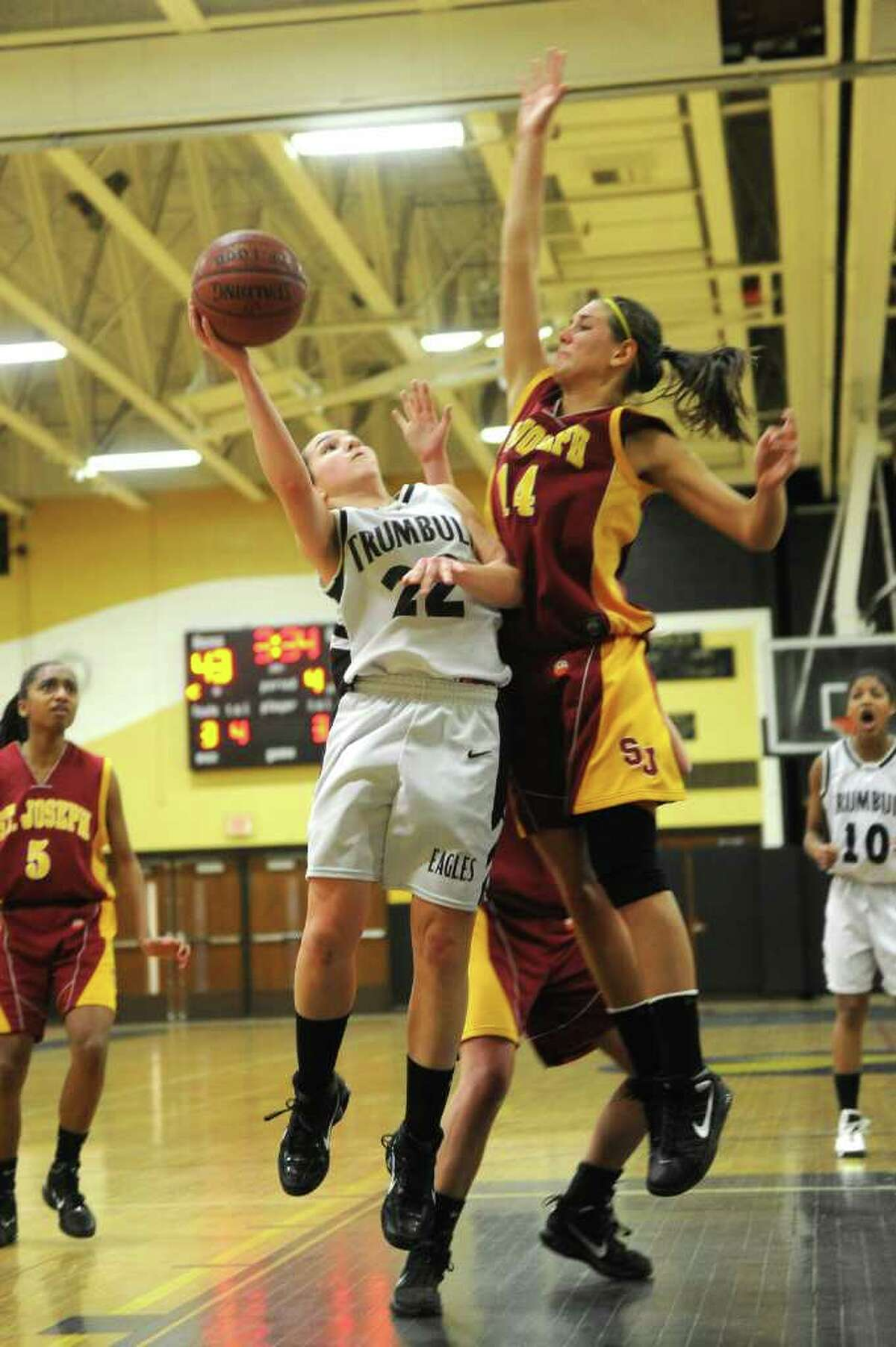 Trumbull's Kelly Coughlin takes a shot as Amaia Gritsko blocks during Tuesday's game at Trumbull High School on January 25, 2011.