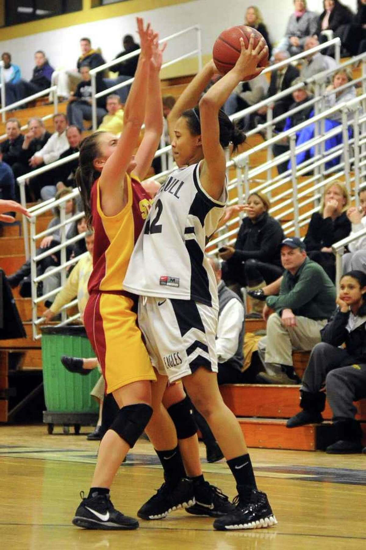 Trumbull's Taisha Lima looks to pass as St. Joseph's Jess Jowdy blocks during Tuesday's game at Trumbull High School on January 25, 2011.